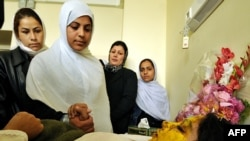 Afghan schoolgirls talk with acid-attack victim Shamsia , 17, as she rests on a hospital bed in Kabul earlier this month.