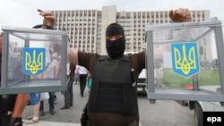 Пророссийский сепаратист в маске держит в руках две урны для голосования с захваченного избирательного участка. Донецк, 23 мая 2014 года.