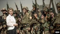 German Defense Minister Ursula von der Leyen (L) stands among Kurdish Peshmerga and German Bundeswehr soldiers during a visit to the educational centre Bnaslawa near Irbil, Septebmer 23, 2016 File photo