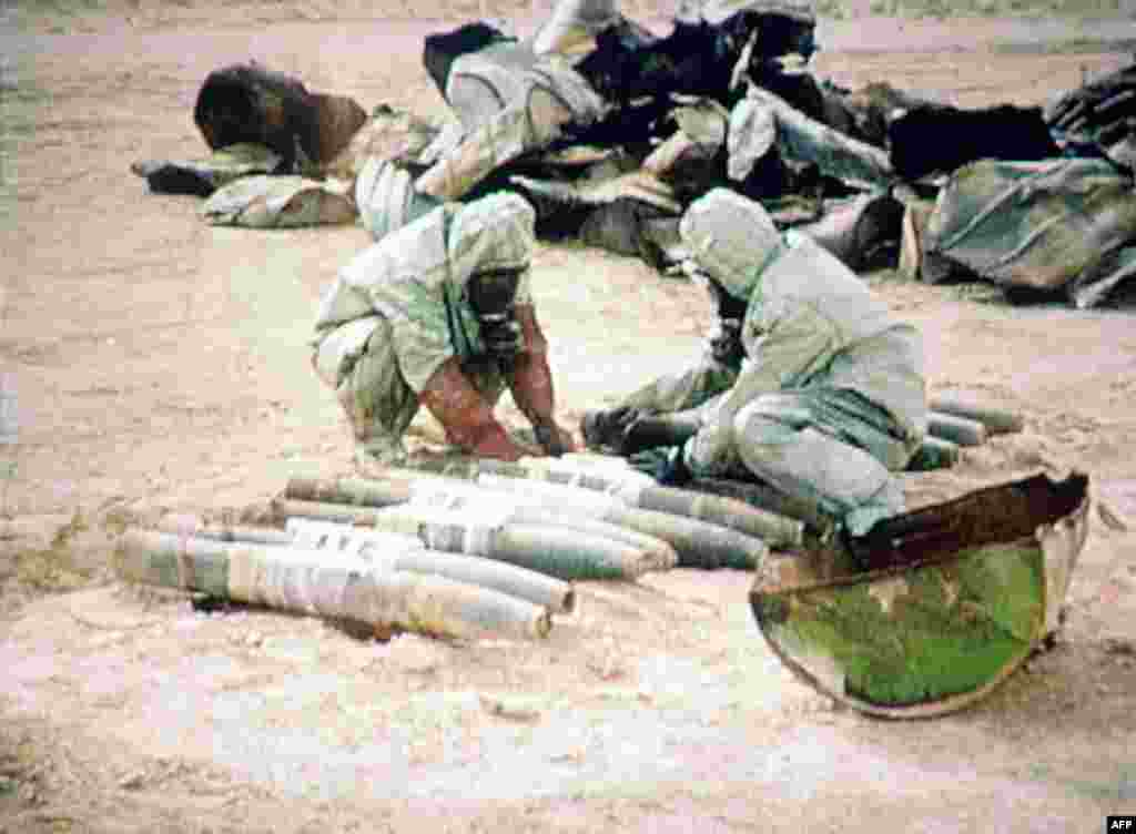 Members of a UN chemical weapons team readies some 1,000 liters of mustard gas for a controlled explosion on November 24, 1992, in Al-Muthanna, Iraq. (Iraqi television)