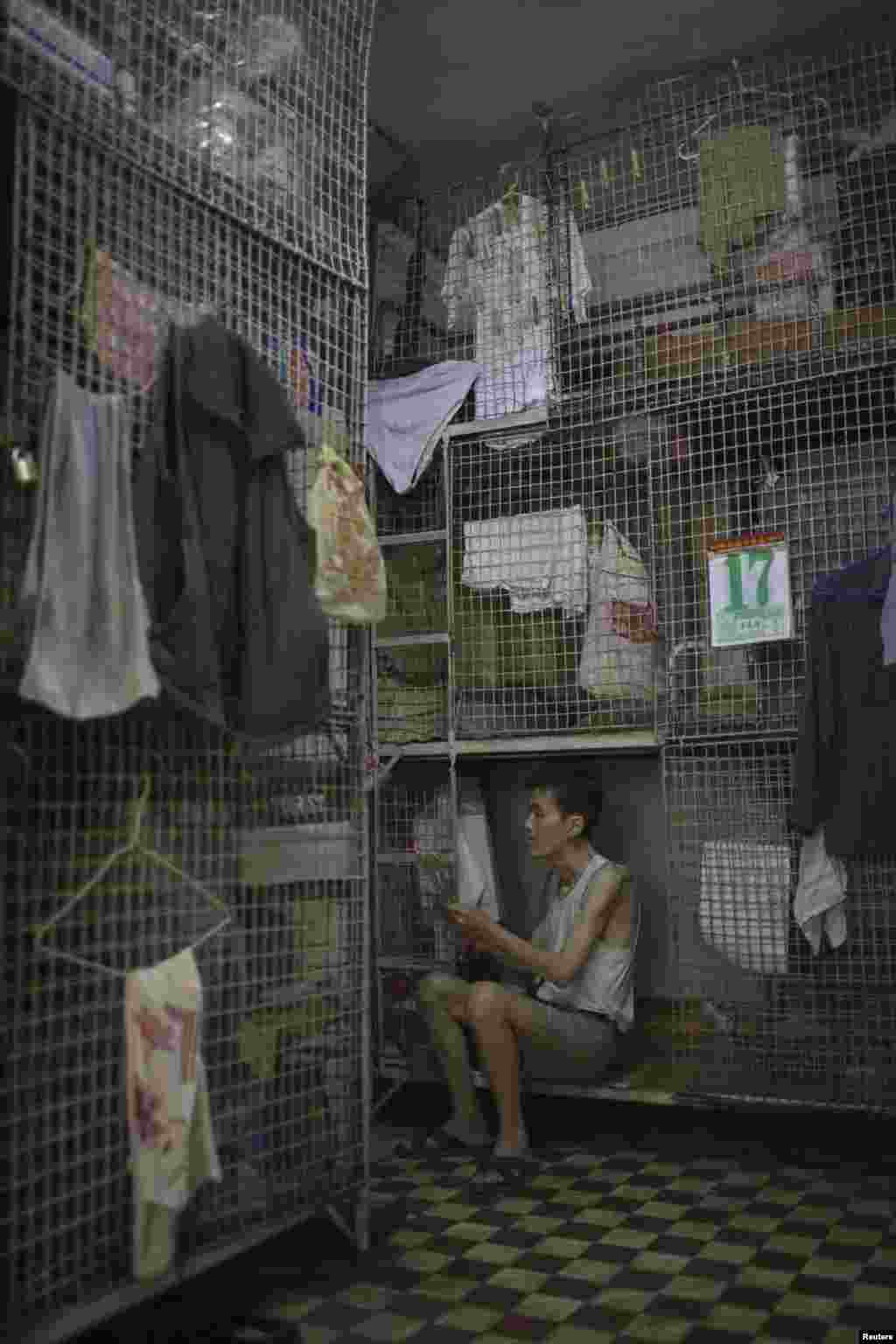 "A man burns incense while sitting in a ""cage home"" in Hong Kong's Tai Kok Tsui district in 2008."