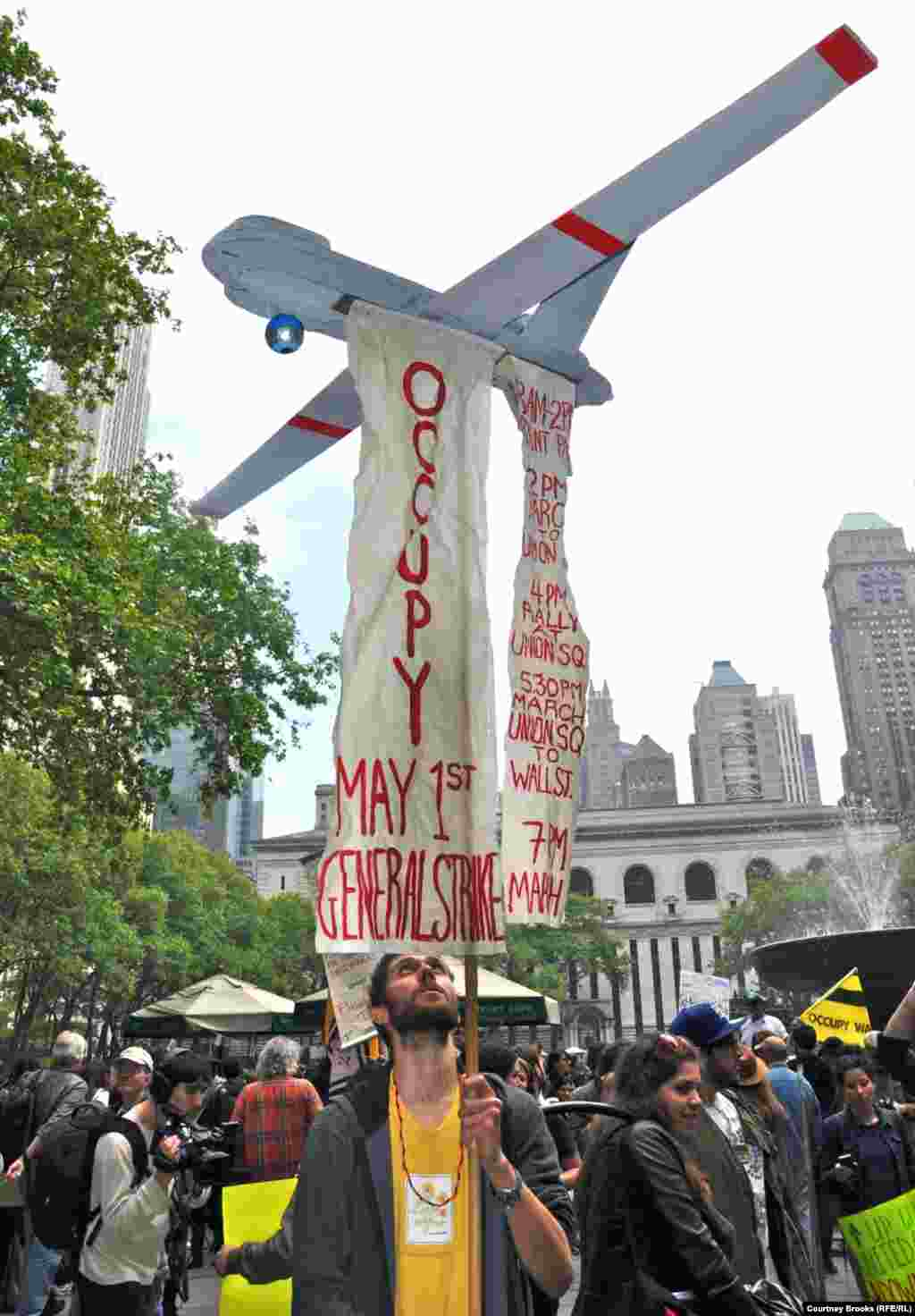 A protester carries an airplane from which hangs the OWS movement's agenda for May 1.