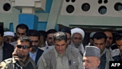 Afghan President Hamid Karzai (right) visits the village of Azizabad in early September.