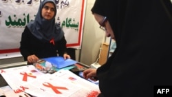 A woman reads a leaflet at an exhibition marking World AIDS Day in Tehran in 2008. Activists are concerned that the calendar change will mean even less public attention paid to an issue that is already a social taboo in Iran.