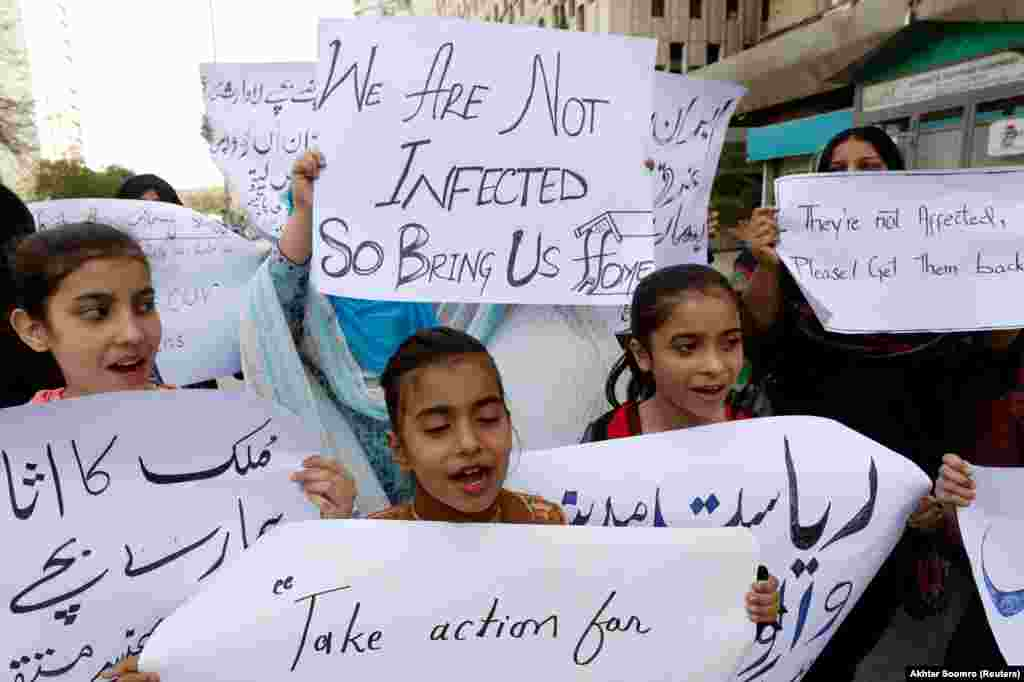 Family members in Karachi hold signs demanding the evacuation of Pakistani students from China who couldn't return after the coronavirus outbreak.