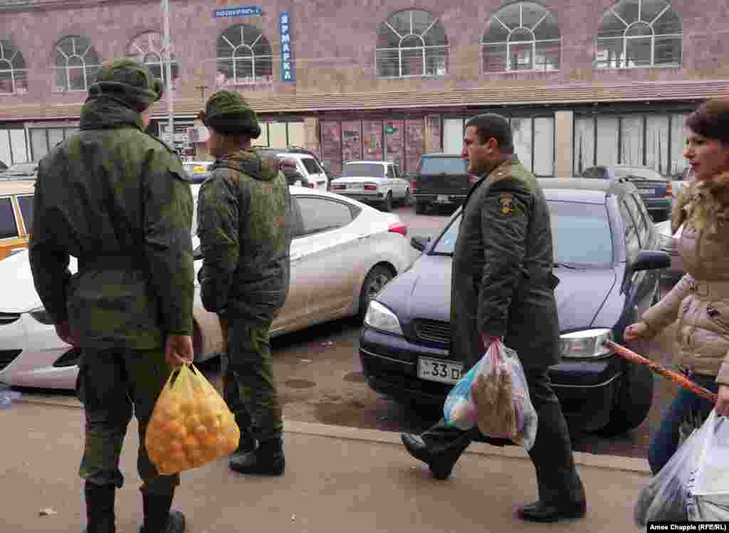 An Armenian Army officer (right) walks past Russian soldiers in Gyumri's center. The officer made eye contact with the soldiers, but no greetings were exchanged.