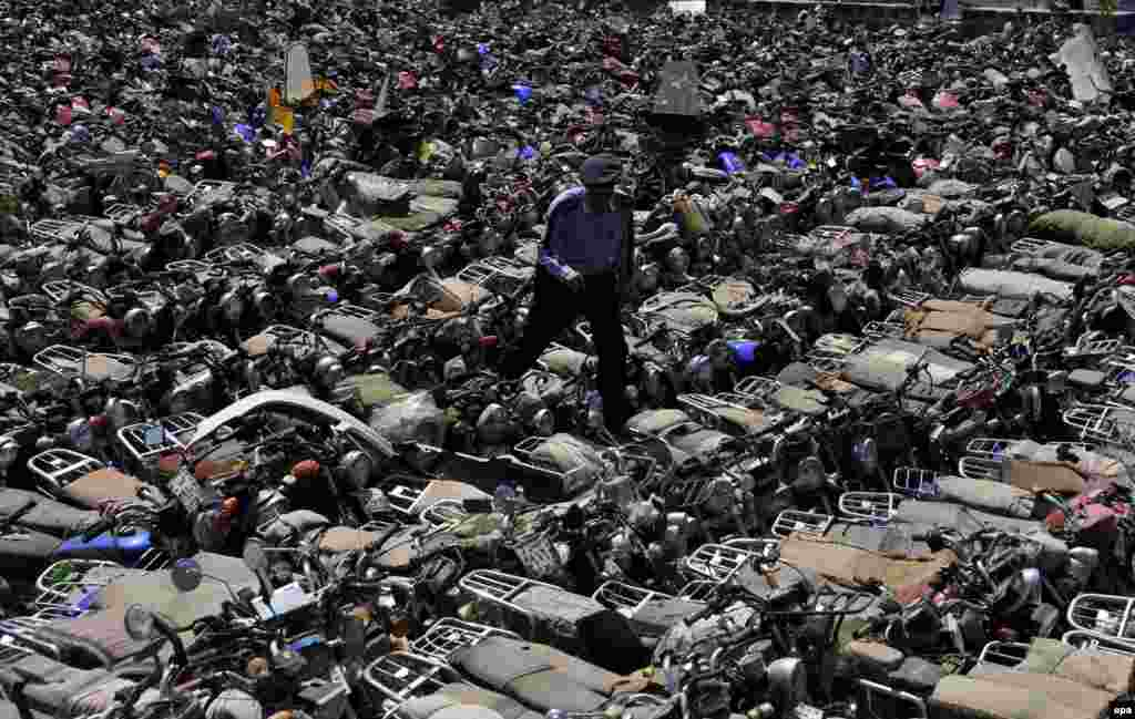 A Yemeni police officer inspects hundreds of seized motorbikes at a police yard in Sanaa. Reports state that Yemeni authorities resumed enforcing a ban on motorbikes used as taxis in Sanaa to prevent Al-Qaeda-linked attacks by motorcyclists on the country's military and security personnel and members of the Shi'ite Houthi movement. (epa/Yahya Arhab)