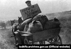 Представитель советской власти везет конфискованное у крестьян зерно на пункт сдачи зерна. Репродукция. УССР, 1933 год