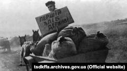 Представник радянської влади везе конфісковане у селян зерно на пункт здачі зерна. Репродукція. Місце і дата зйомки: УССР, 1933 рік