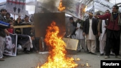 Afghans protesters burn posters of Iran's leaders during a demonstration in Jalalabad Province.