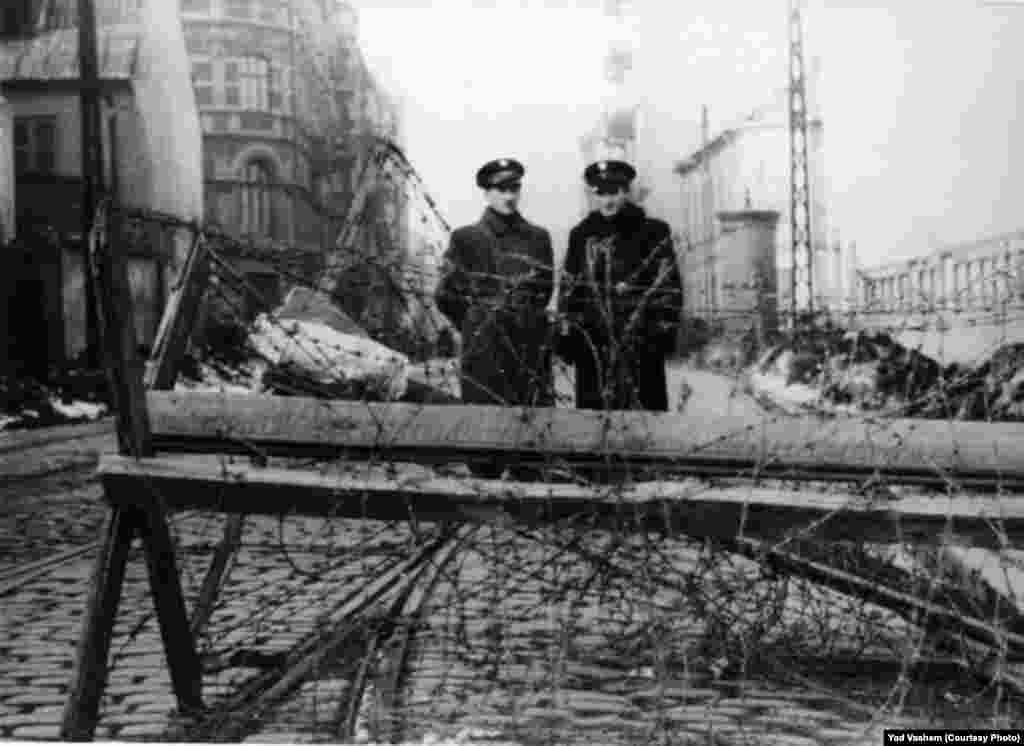 Two Jewish policemen stand near barbed-wire fences.