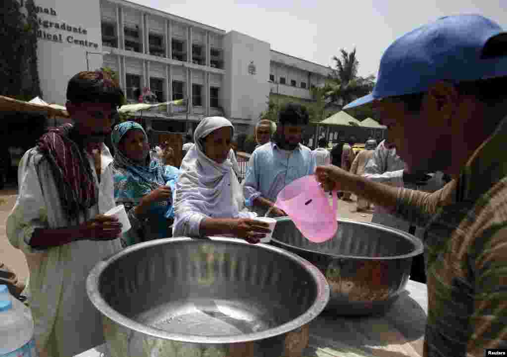 People receive drinking water from volunteers during the intensely hot weather in Karachi on June 23.
