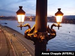 Winged dragons hold the lanterns of Budapest's Margaret Bridge at dusk.