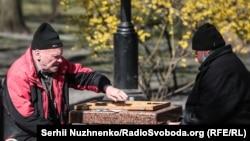 Чоловіки грають в шахи на свіжому повітрі в київському парку. 4 квітня 2020 року