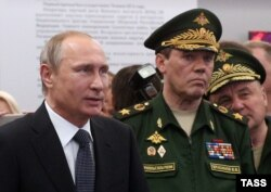 Начальник Генштабу Збройних сил Росії, заступник міністра оборони Росії, генерал армії Валерій Герасимов (в центрі) з президентом Росії Володимиром Путіним (ліворуч). 16 червня 2015 року