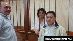 Юрист Наталья Соколова за решеткой в зале суда. Слева от нее - муж Василий Чепурной, справа адвокат Арман Жаменов. Актау, 26 сентября 2011 года.
