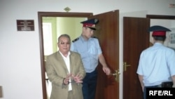 Полицейские выводят в наручниках бывшего советника акима Западно-Казахстанской области Алпамыса Бектурганова в наручниках из зала суда. Уральск, 13 августа 2009 года.