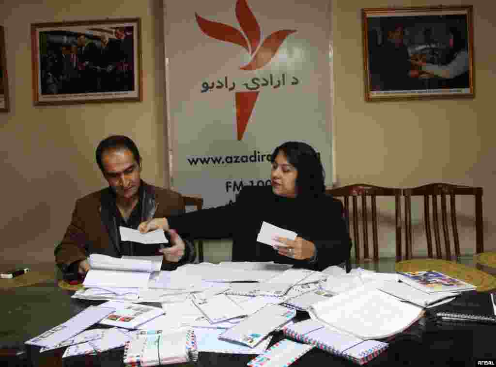 Radio Azadi employees look at letters sent in to the radio station by Afghan listeners