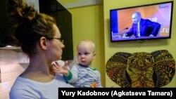 Ілюстраційне фото. Жінка тримає свого сина та дивиться телевізійну трансляцію щорічної прес-конференції російського президента Володимира Путіна в Москві, 14 грудня 2017 року