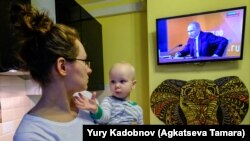 A woman holds her son as she watches a TV broadcast of Russian President Vladimir Putin's annual press conference in Moscow on December 14.