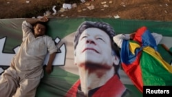 "Supporters of Imran Khan, the head of the Pakistan Tehrik-e Insaf political party, take a nap on Khan's campaign banner during what has been dubbed a ""freedom march"" in Islamabad on August 25."