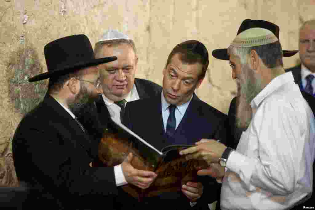 Russian Prime Minister Dmitry Medvedev (center) looks into a book presented to him during a visit to the Western Wall in Jerusalem on November 10. (Reuters/Dan Balilty)