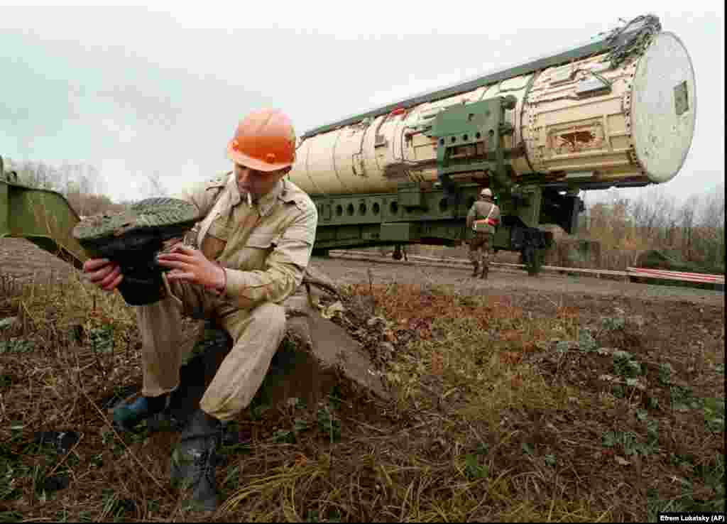 A Ukrainian officer smokes and shakes sand out of his boot before preparing to blow up a missile silo near the town of Derazhnya in central Ukraine, October 23, 1996.