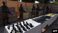 Пакистанские военнослужащие у стендов с партией изъятого оружия.