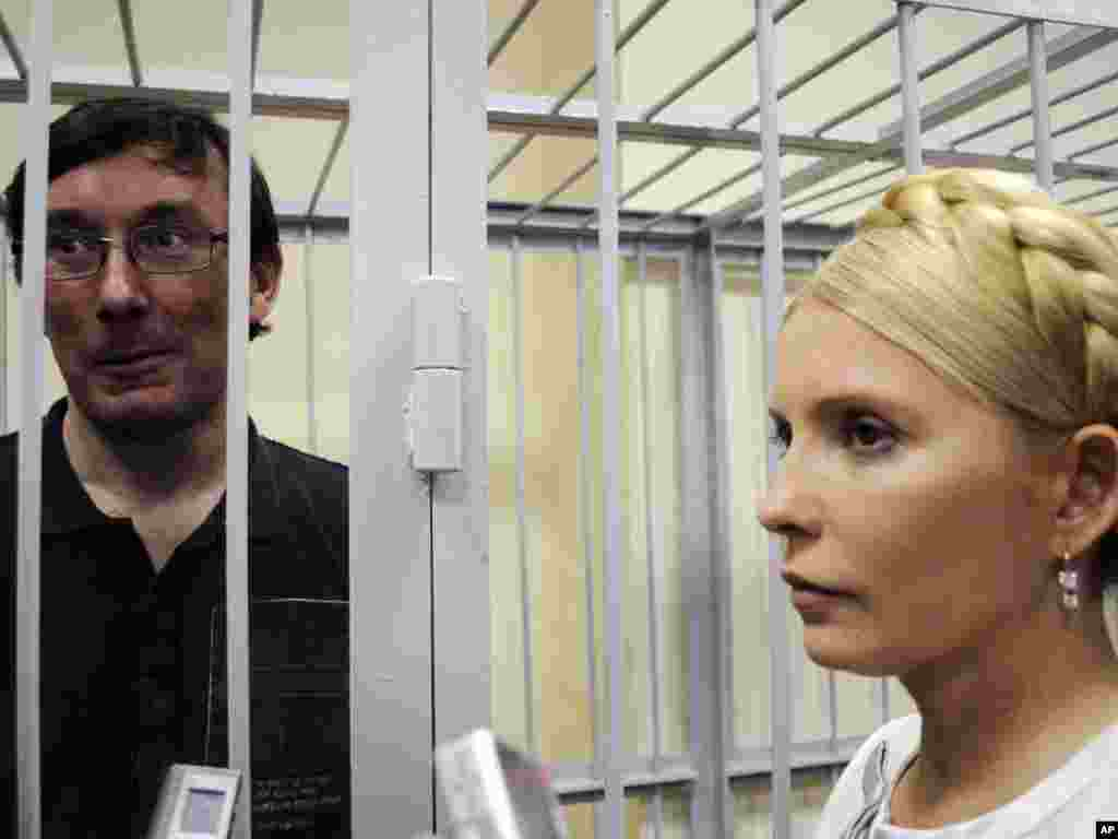 Former Ukrainian Interior Minister Yuriy Lutsenko seen in a defendant's cage as former Ukrainian Prime Minister Yulia Tymoshenko stands at right in a courtroom in Kyiv on May 23. Tymoshenko's top ally was detained in late December on charges of abuse of office. Photo by Sergei Chuzavkov for AP