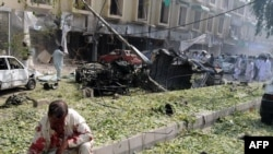 A victim of the Peshawar suicide bombing awaits assistance as people scour the site for other injured countrymen.