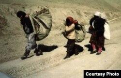 Люди с вещами идут по дороге во время гражданской войны в Таджикистане с 1992 по 1997 год.