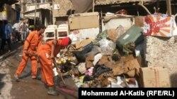 عمال البلدية يرفعون نفايات في مدينة الموصل