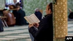 Мечитте Куран окуп отурган адам.