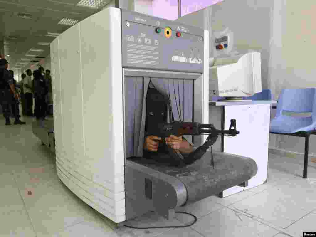 A Hamas fighter takes position inside a scanning machine in the customs hall of the Rafah crossing border, between Egypt and the southern Gaza Strip, after they captured it, June 15, 2007. REUTERS/Ibraheem Abu Mustafa