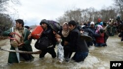 Біженці перетинають річку, прямуючи до Македонії з табору на грецько-македонському кордоні, 14 березня 2016 року