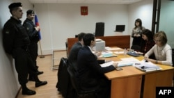 Court officials and lawyers attend the hearing of the Golos NGO in Moscow on April 25.