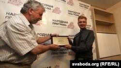 Аляксандар Мілінкевіч уручае прэмію Лявону Вольскаму
