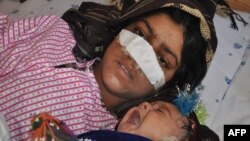 Afghan woman Reza Gul, 20, and whose nose was sliced off by her husband in an attack, lies on a bed with her baby as she receives treatment at a hospital in the northern Afghanistan on January 19.