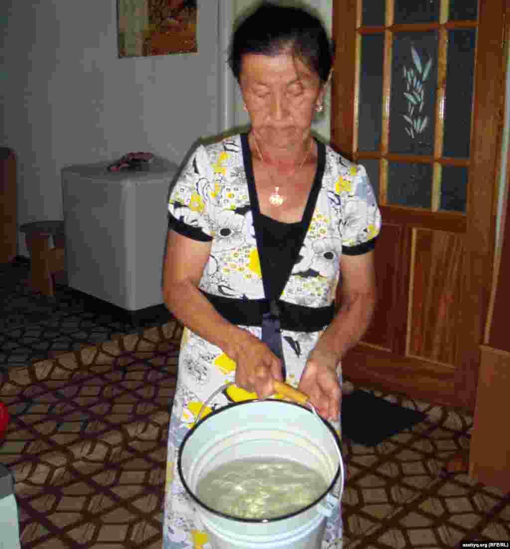 Жительница Шубарши Умсынай Кудиярова говорит, что в селе Шубарши экология плохая. На фото: Умсынай Кудиярова показывает грязную воду в ведре из колодца. Шубарши, 14 мая 2012 года.