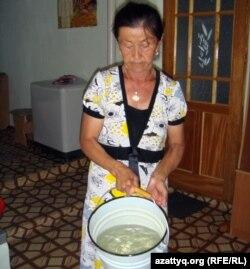 Жительница села Шубарши Умсынай Кудиярова показывает ведро воды.