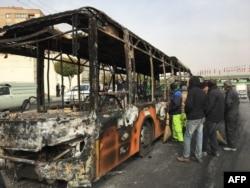 Жанармайдың қымбаттауына жаппай наразылық кезінде өртенген автобустың қаңқасына қарап тұрған адамдар. Исфахан, Иран, 17 қараша 2019 жыл.