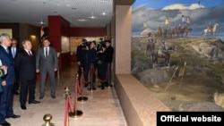 Қазақстан президенті Нұрсұлтан Назарбаев (ортада) пен қорғаныс министрі Иманғали Тасмағамбетов (сол жақта) жаңадан ашылған әскери-тарихи музейдегі қабырғаға салынған суретке қарап тұр. Астана, 1 желтоқсан 2015 жыл. Сурет президенттің ресми сайтынан алынды.
