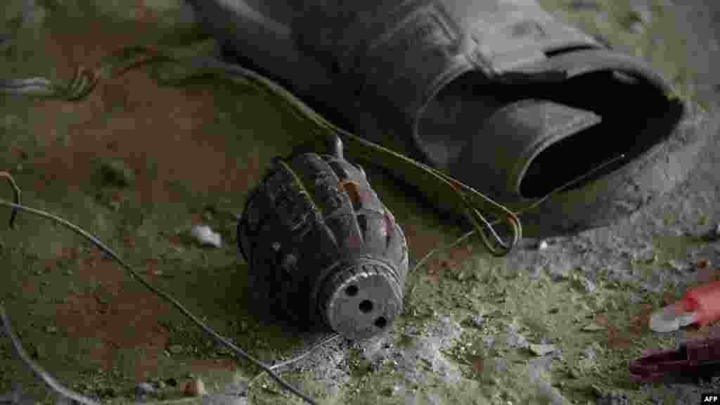 A grenade lies on the floor next to a sandal inside the building where Taliban militants launched an attack in Kabul on April 15. (AFP/Johannes Eisele)