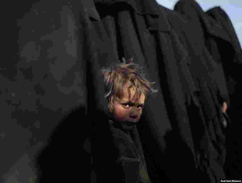 A boy looks at the camera near Baghouz, Deir Al Zor Province, Syria. (Reuters/Rodi Said)