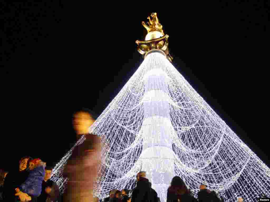 People pose for pictures near the Freedom Monument, which has been illuminated with Christmas decorations, on the main square in Tbilisi on December 1. Photo by David Mdzinarishvili for Reuters