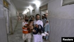 Pakistan -- A man carries a child, who was injured in a suicide bomb attack, to the Lady Reading Hospital for treatment in Peshawar, 21Jun2013