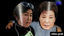 Активісти за відставку президента Південної Кореї одягли фотомаски із зображенням Пак Кин Х'є та її подруги-фігуранта корупційного скандалу