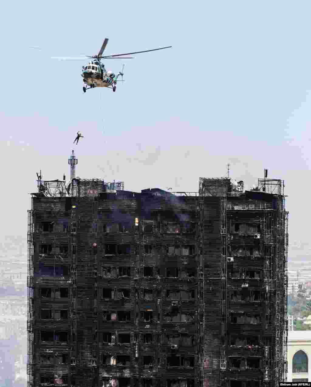 A rescue worker abseils from a helicopter during rescue attempts at a large fire in a high-rise apartment building in Baku. At least 15 people died in the blaze. (Ehtiram Jabi/RFE/RL)