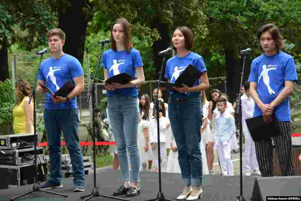 Группа молодых людей в футболках с логотипом Фонда Дениса Тена декламируют цитаты из стихотворений Дениса Тена. Алматы, 22 июня 2019 года.