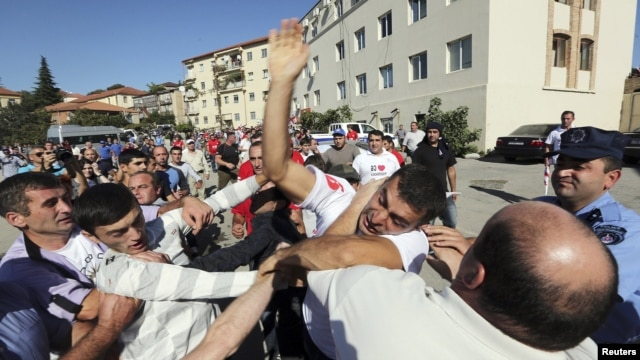 Supporters of the ruling United National Movement scuffle with supporters of the opposition Georgian Dream coalition during an election rally last week in the town of Signagi. Can the opposition consolidate a peaceful transition, and will the ruling party let them?